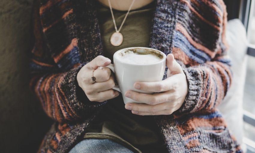Vrouw in wollen vest met cappuccino