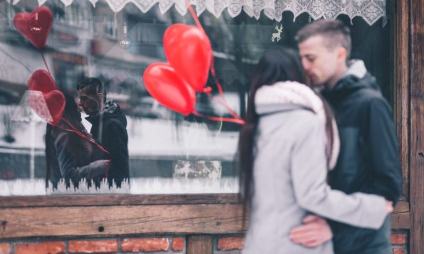 Jongen en meisje samen buiten met rode ballonnen