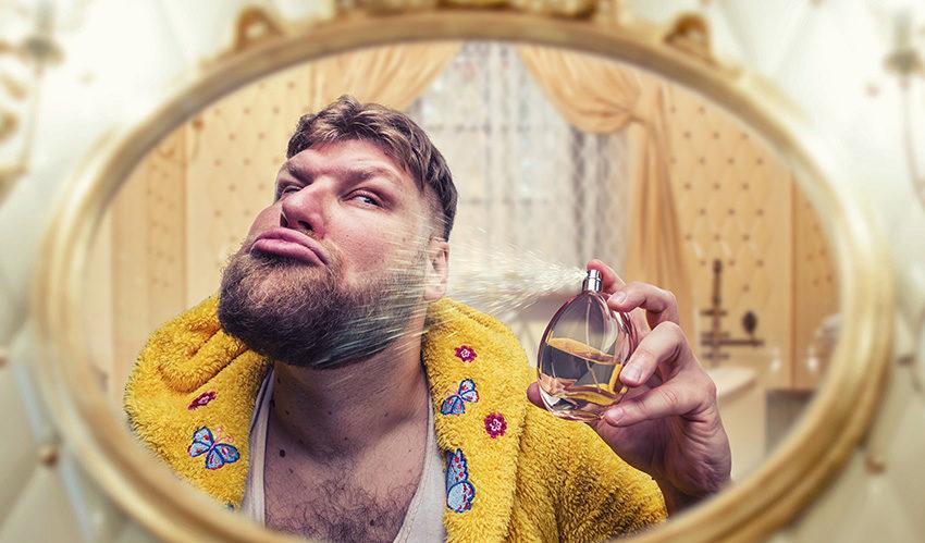 Man in badkamer spuit met fles parfum