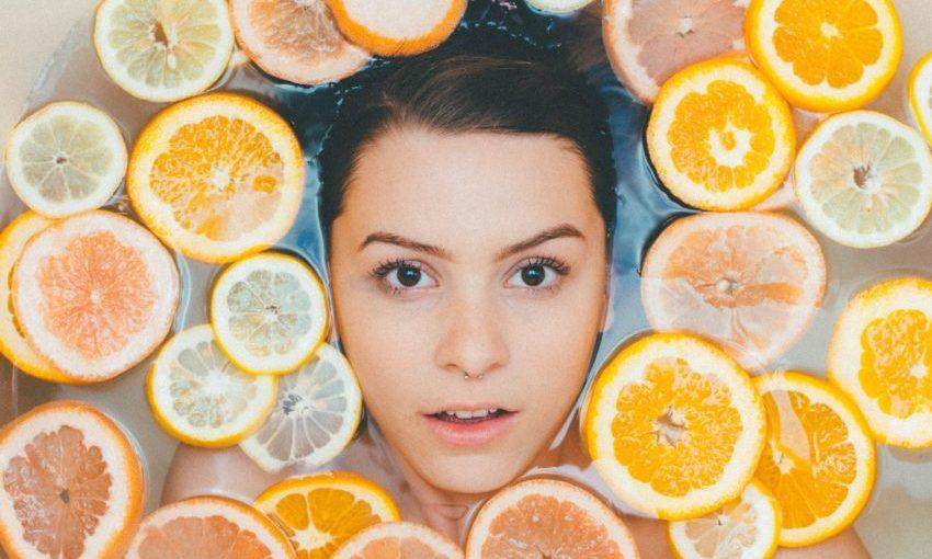 Jonge vrouw in bad met sinaasappels rond gezicht